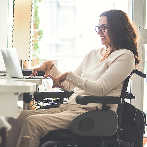 Side view of a happy woman with physical disability working on a laptop in the office.